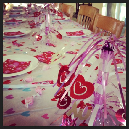 Table preparations for Valentine-themed dinner